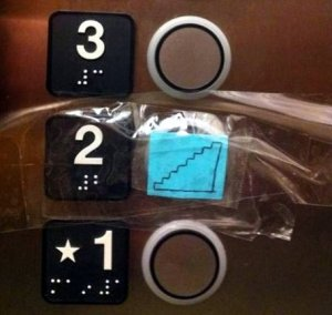 Photo of elevator buttons. The button for the second floor has a drawing of stairs taped over it so the button is unusable and the braille is unreadable.